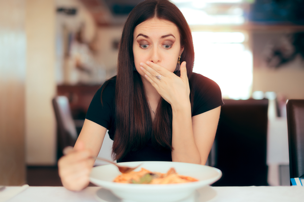 女性が食べ物を食べて苦しそうにしている