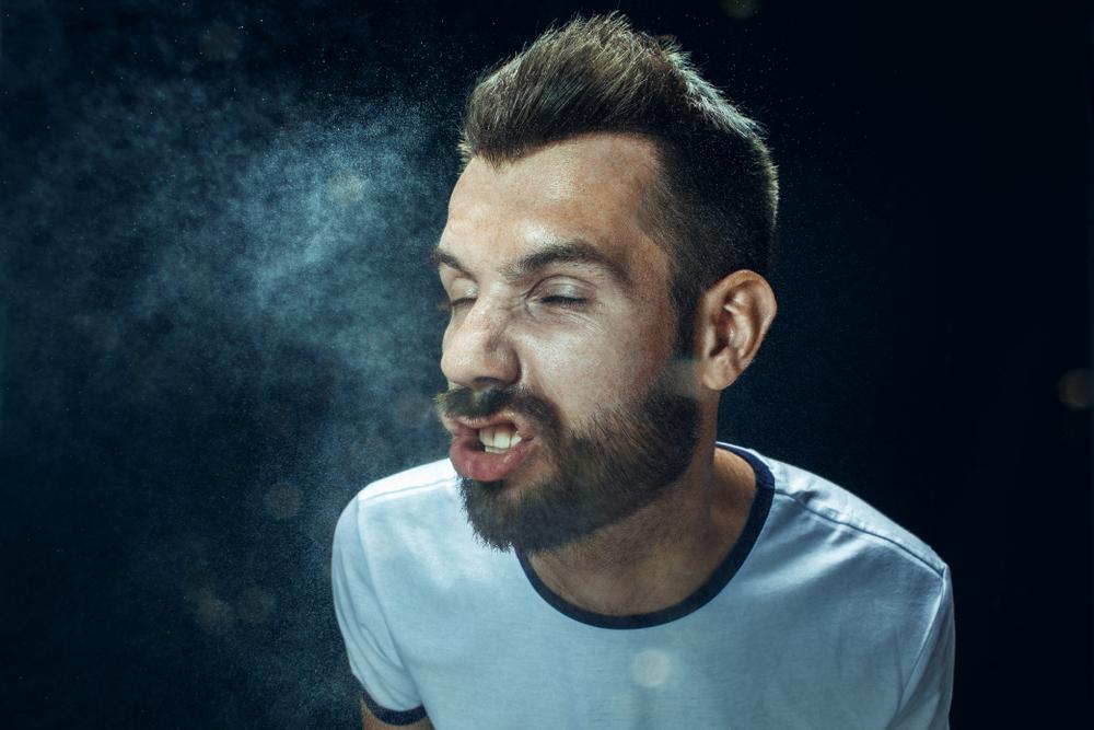 男の人がくしゃみをしてウイルスを拡散している